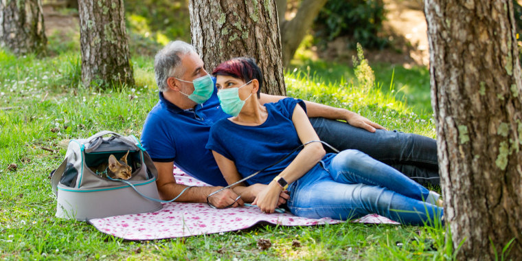 Couple on picnic wearing face masks with their cat. Shop picnic essentials for a day in the park, backyard or roof, including a picnic basket, face mask, hand sanitizer, sunscreen and more.