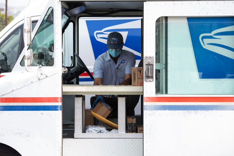 Image: A postal worker delivers mail in Los Angeles on April 29, 2020.