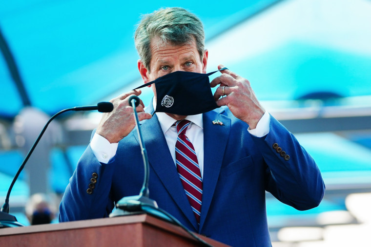 Gov. Brian Kemp puts on a mask after speaking at a press conference announcing statewide expanded COVID testing on Aug. 10, 2020, in Atlanta.