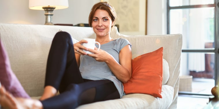 Woman relaxing on couch wearing black leggings
