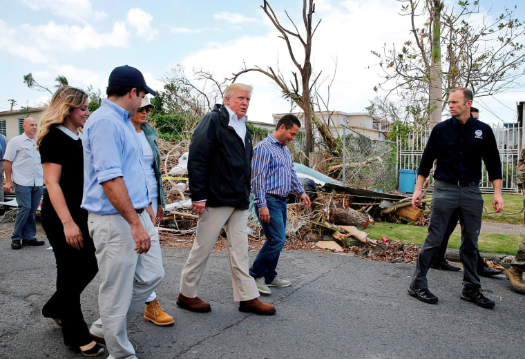 Image: President Trump walks past hurricane wreckage as he visits areas damaged by Hurricane Maria in Guaynabo, Puerto Rico