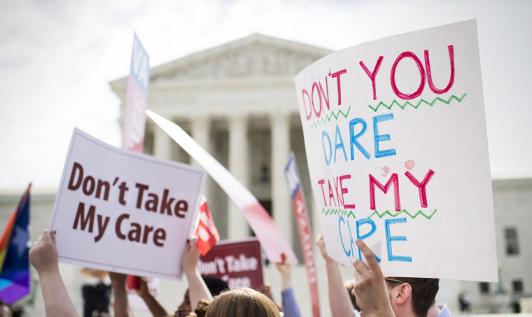 Affordable Care Act supporters hold up signs outside the Supreme Court on June 25, 2015.