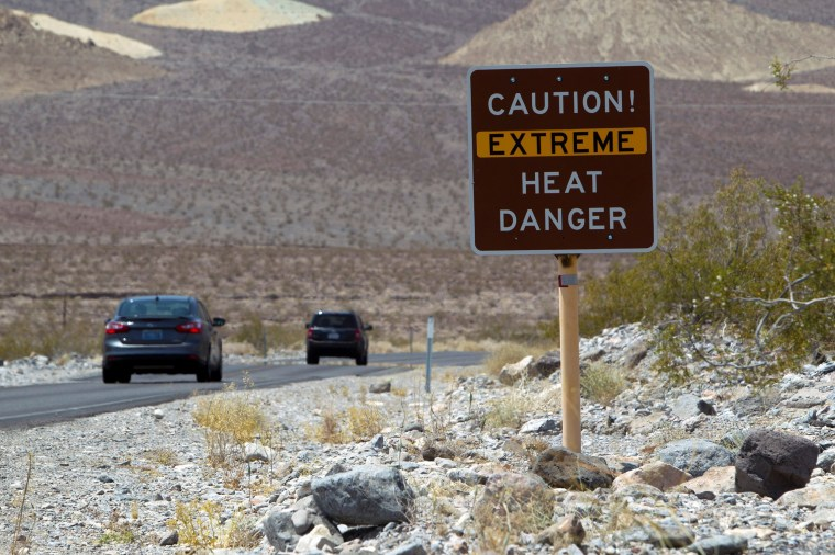 Image: A sign warns of extreme heat as tourists enter Death Valley National Park in California.