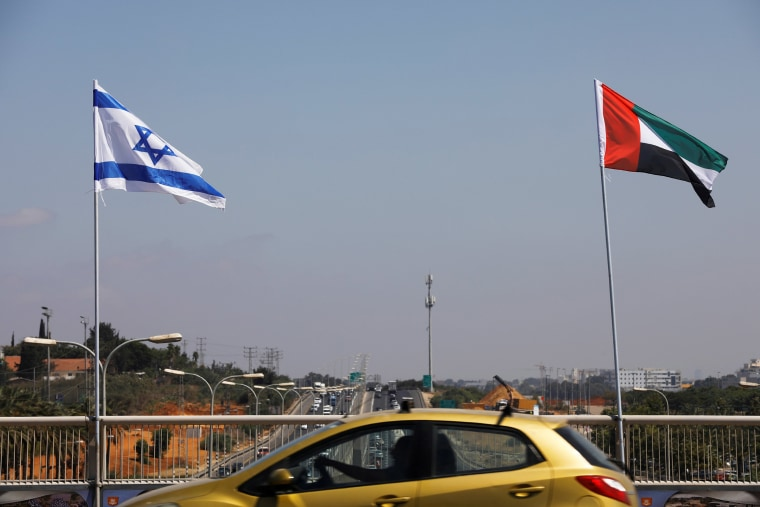 Image: A car drives near the national flags of Israel and the United Arab Emirates as they flutter along a highway following the agreement to formalize ties between the two countries, in Netanya