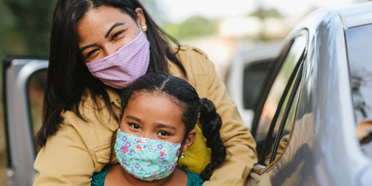 A woman and a girl outdoors wearing colorful and patterned cloth face masks.