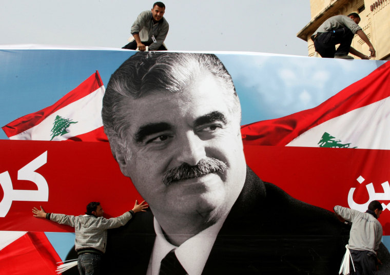 Image: FILE PHOTO: Workers prepare a giant poster depicting Lebanon's assassinated former prime minister Rafik al-Hariri, in downtown Beirut