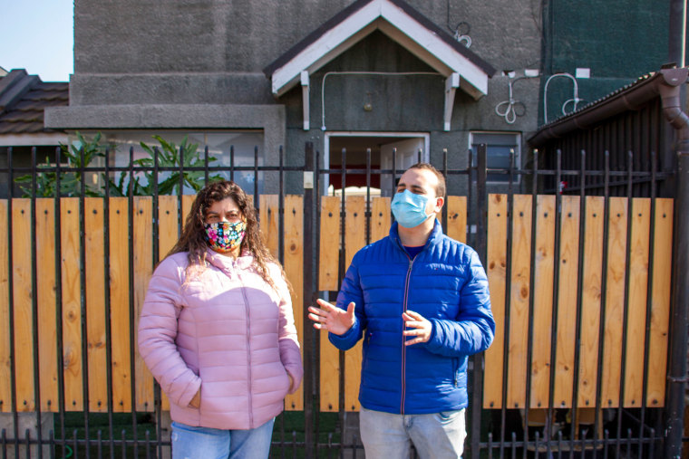 Cristabel L?pez, 43, and her son, Felipe, 26, in front of their home in a Santiago suburb.