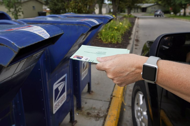 A person drops applications for mail-in ballots into a mailbox in Omaha, Neb., on Aug. 18, 2020.