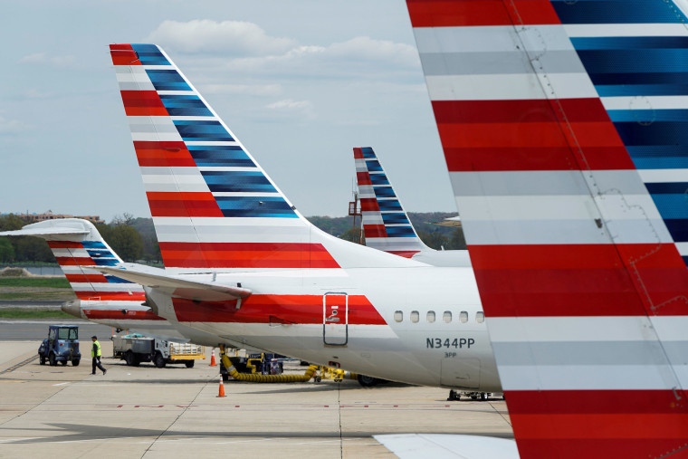 Image: A member of a ground crew walks past parked American Airlines planes.