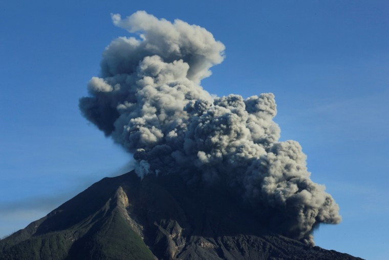 Image: Mount Sinabung volcano spews volcanic material as seen from Tiga Pancur village in Karo