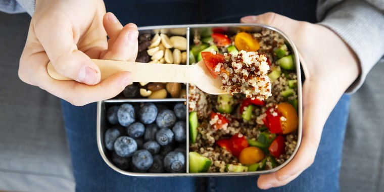 Lunchbox with quinoa salad with tomato and cucumber, blueberry and trail mix