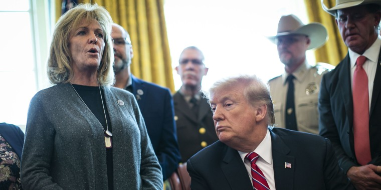 Mary Ann Mendoza speaks as U.S. President Donald Trump listens during a veto signing in the Oval Office of the White House on March 15, 2019.