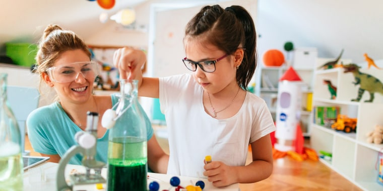 Mother and young daughter doing science experiment at home