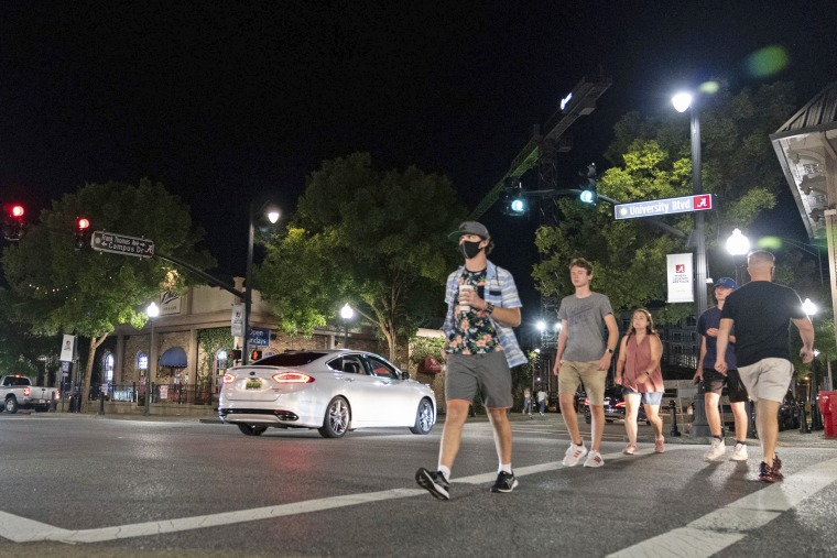 """People make their way along """"The Strip,"""" an area of bars and restaurants near the University of Alabama in Tuscaloosa on Saturday."""
