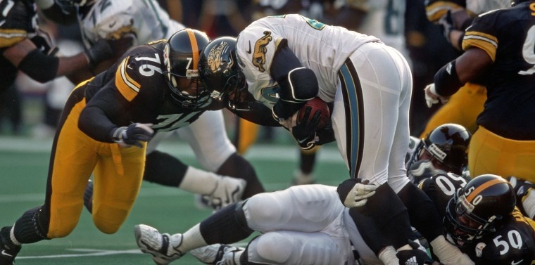 Image: Defensive lineman Kevin Henry #76 and linebacker Earl Holmes #50 of the Pittsburgh Steelers tackle running back Fred Taylor #28 of the Jacksonville Jaguars during a game at Three Rivers Stadium