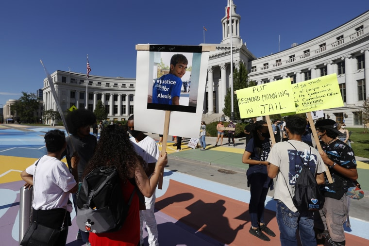 Demonstrators hold placards during a protest over the Denver District Attorney Beth McCann's handling of the shooting death of 16-year-old Alexis Mendez-Perez on June 26, 2020.