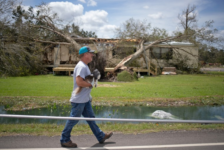 Image: Man holds his dog as he walks to his residence in aftermath of Hurricane Laura in Sulphur, Louisiana