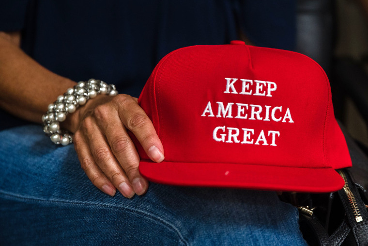 """Image: Deborah Palomba holds a \""""Keep America Great\"""" hat as she watches the Republican National Convention on TV in the office of San Diego County's Republican Party in Rancho Bernardo, California"""
