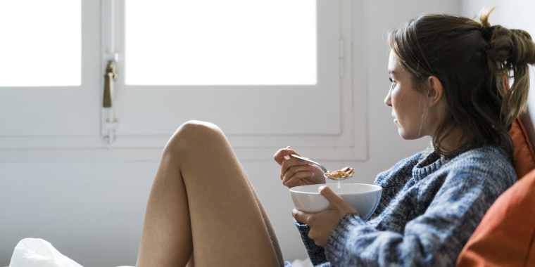 Serious young woman eating cereals in bed