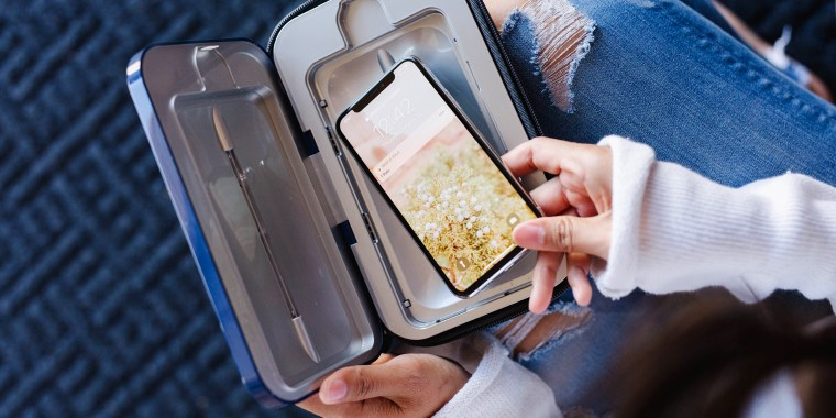 Woman putting smartphone in PhoneSoap UV sanitizer