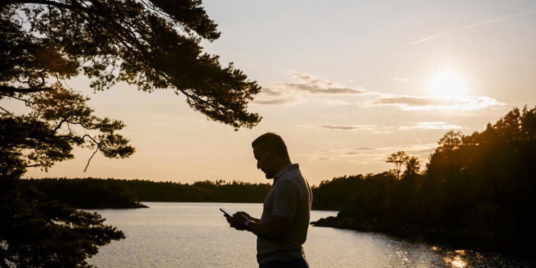 Silhouette man using smart phone while standing at lake during sunset