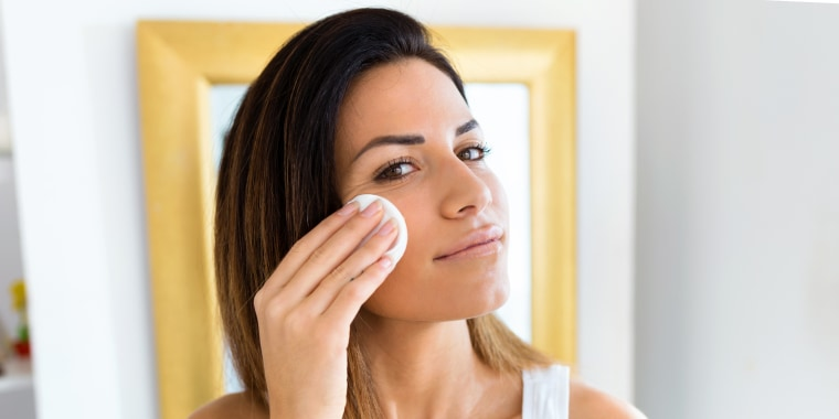 Woman applying toner with cotton pad