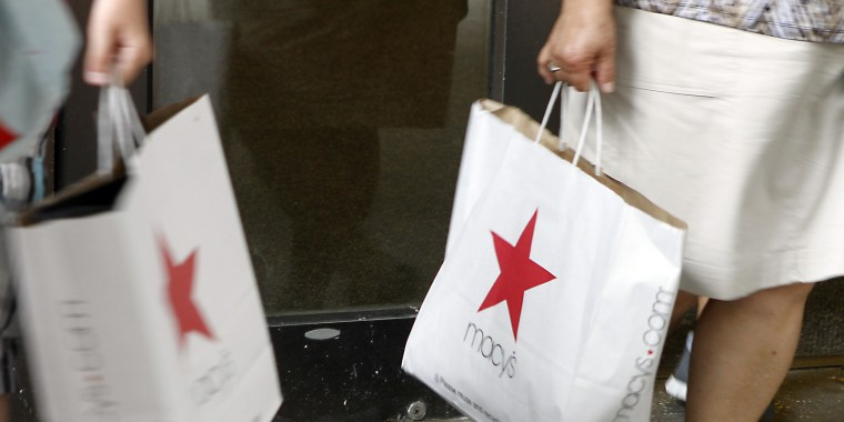 A shopper in New York carries a Macy's shopping bag.