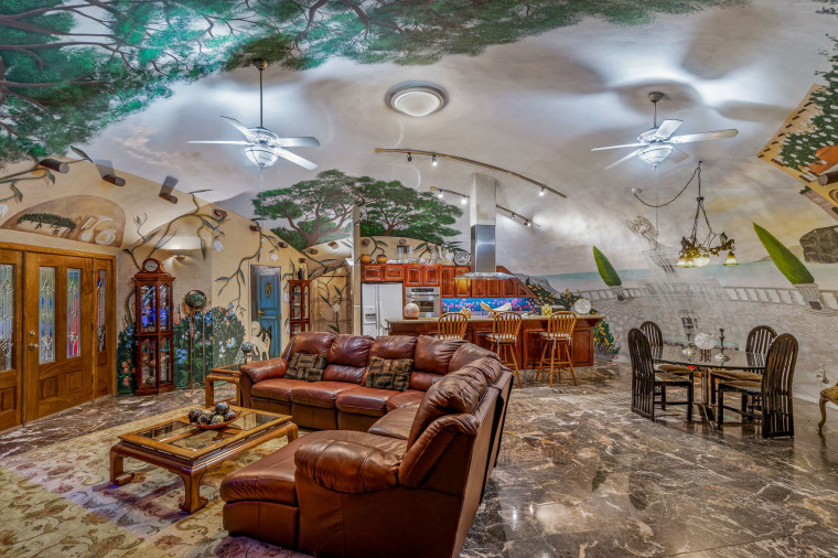 Phần chính của ngôi nhà bao gồm nhà bếp, khu vực ăn uống và phòng khách, với các tác phẩm nghệ thuật đầy màu sắc trên tường.