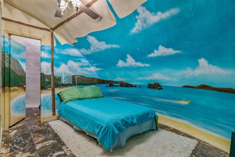 Một phòng ngủ có họa tiết bãi biển nhiệt đới với bộ khăn trải giường màu xanh mòng két phù hợp.