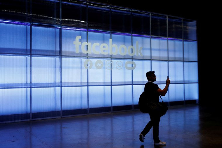 Image: An attendee takes a photograph of a sign during Facebook Inc's F8 developers conference in San Jose, California
