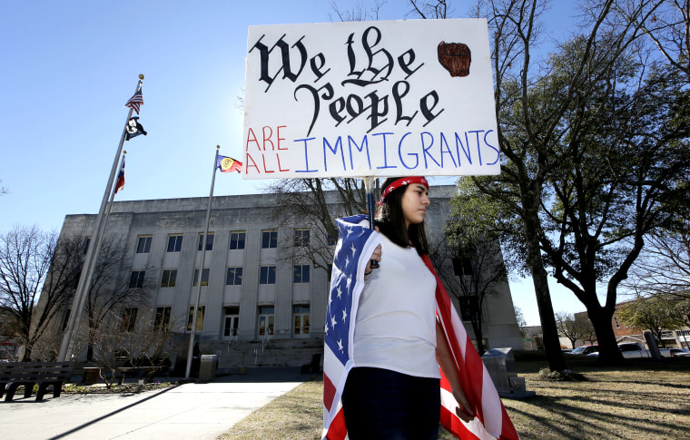 A high school senior holds a sign outside the Grayson County Courthouse during an action called A Day Without Immigrants in Sherman, Texas, on Feb. 16, 2017.