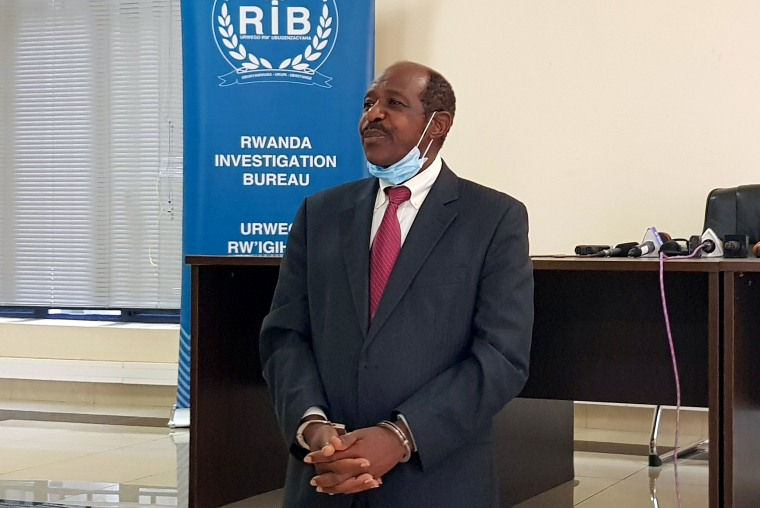 Image: Rusesabagina is detained and paraded in front of media in handcuffs in Kigali