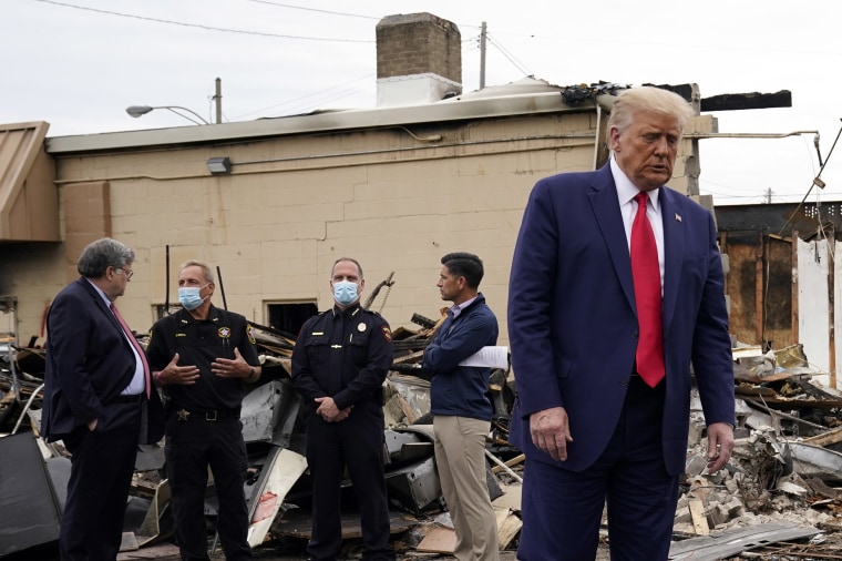 Image: President Donald Trump turns around after talking with law enforcement officials Tuesday, Sept. 1, 2020, as he tours an area damaged during demonstrations after a police officer shot Jacob Blake in Kenosha