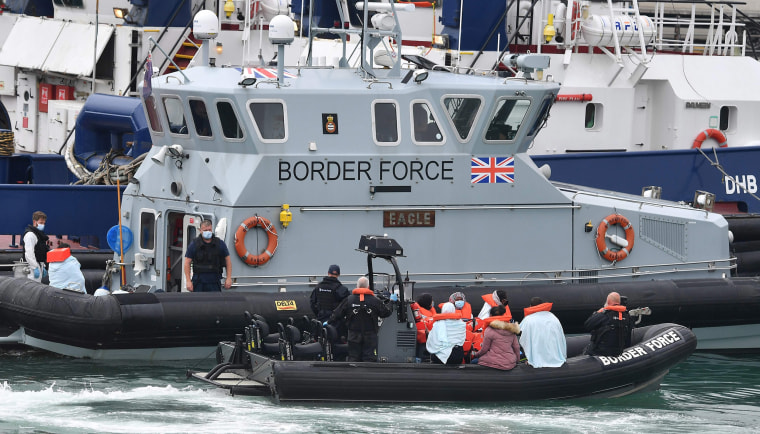 Image: UK Border Force officials travel in a RIB with migrants picked up at sea whilst crossing the English Channel, as they arrive at the Marina in Dover, southeast England