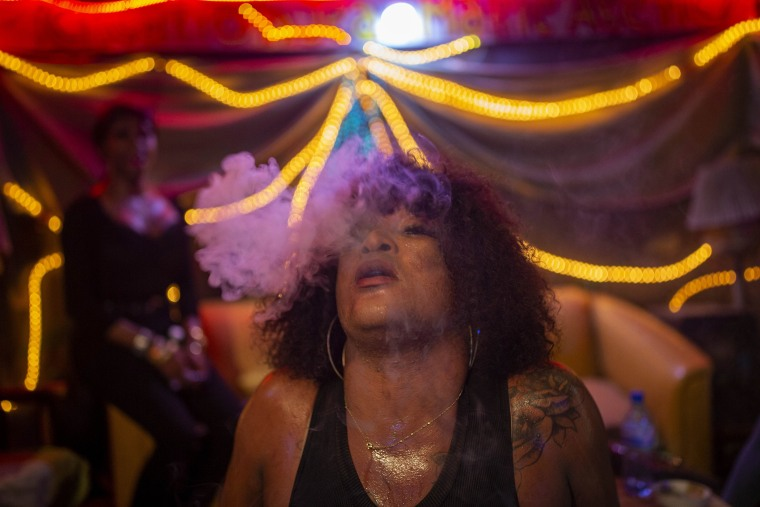 Image: Transgender Laurent Voltus, a resident at the Kay Trans Haiti center, exhales cigarette smoke while dancing with friends at a club in Port-au-Prince, Haiti