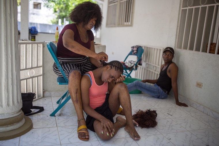 Image: Transgender Laurent Voltus braids the hair of her roommate Vlajimy Cesar as they sit on the porch of the Kay Trans Haiti center where they live, in Port-au-Prince, Haiti