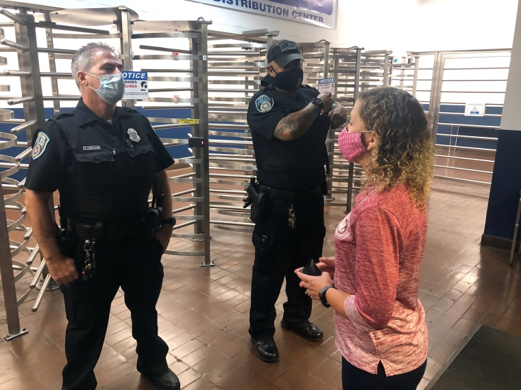 Two U.S. Postal Inspection Service officers block Rep. Debbie Wasserman Schultz, D-Fla., from entering the Miami Processing and Distribution Center in the early morning hours of Sept. 4.