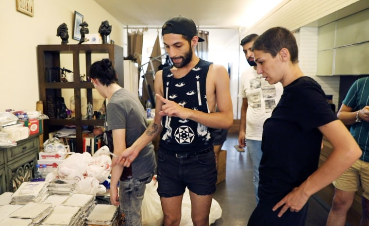 LGBTQ activist and bar owner Sandra Melhem, right, organizes the distribution of food and supplies with volunteer Firas Naboulsi in Melhem's Beirut home