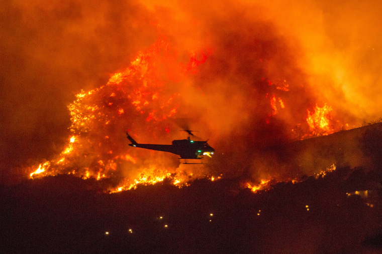 A helicopter prepares to drop water at a wildfire in Yucaipa, Calif., on Saturday as three fast-spreading wildfires sent people fleeing, one of them trapping campers at a reservoir in Sierra National Forest.