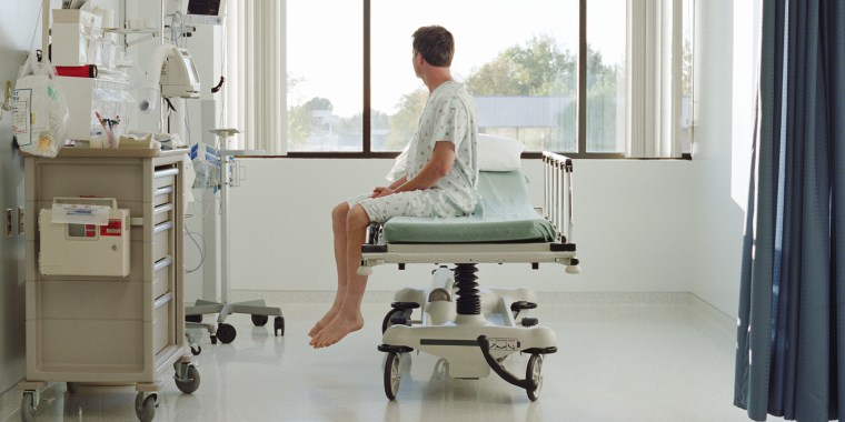 Man in examination gown sitting on bed in hospital room, side view