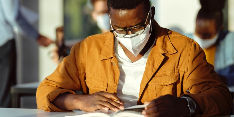 African American college student with face mask reading a book in the classroom.