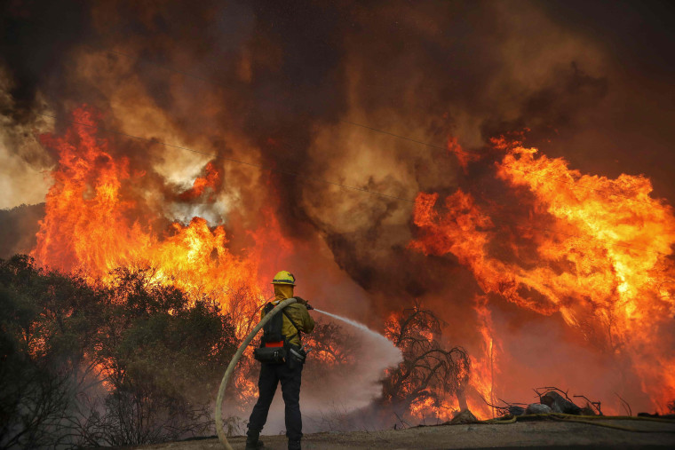 Image: San Miguel County Firefighters battle a brush fire along Japatul Road during the Valley Fire in Jamul, California