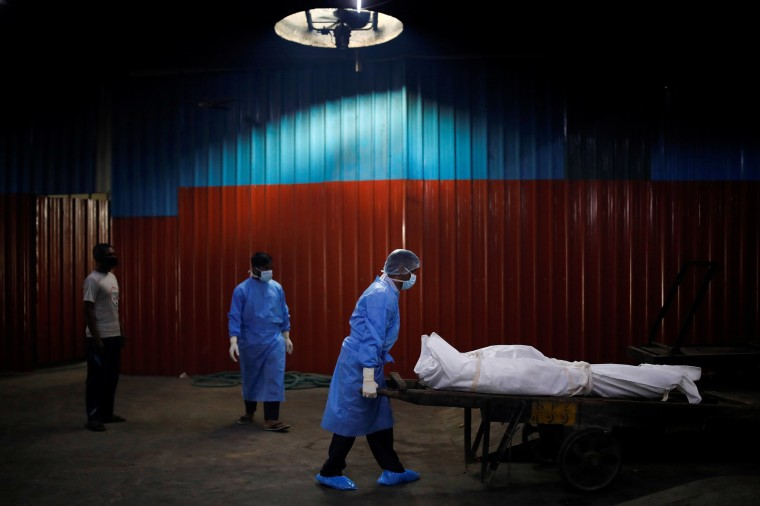 Image: A health worker wearing personal protective equipment (PPE) carries the body of a man, who died due to the coronavirus disease (COVID-19), at a crematorium in New Delhi