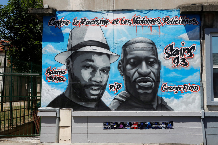 Image: Street art paying tribute to George Floyd and Adama Traore a black man who died in police custody in 2016, on a wall in a street of Stains, in the outskirts of Paris