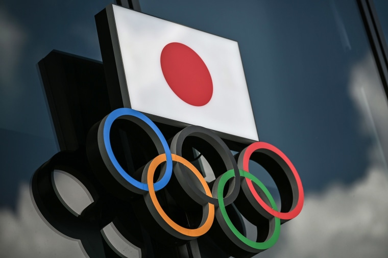 Image: Olympic Rings and the Japanese flag are seen outside the Olympic Museum in Tokyo