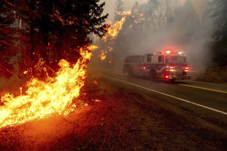 Image: A firetruck drives along state Highway 168 while battling the Creek Fire in the Shaver Lake community of Fresno County, Calif