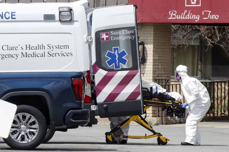 Healthcare officials load a patient into an ambulance at Andover Subacute and Rehab Center in Andover, New Jersey