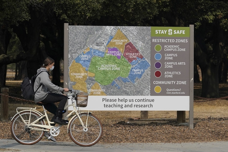 Image: A bicyclist rides past a sign showing restricted zones around the Stanford University campus in Stanford, CA.