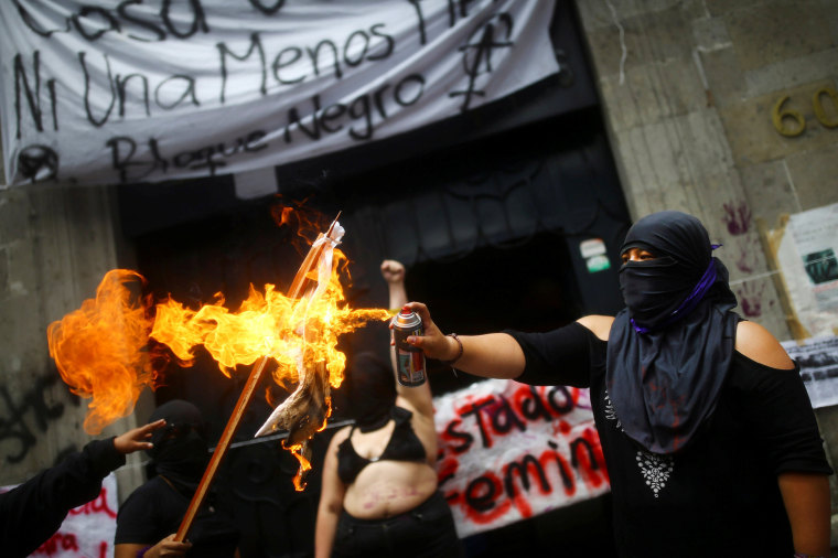Image: A feminist activist burns a flag outside the National Human Rights Commission building after seizing the facilities of the organization for demand justice for the victims of gender violence and femicide in Mexico City