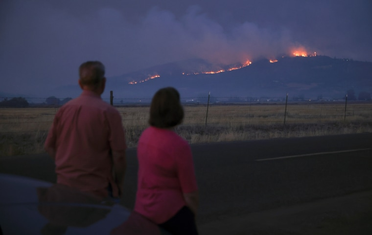 Image: Local residents look at smoke and fire over a hill during wildfires near the town of Medford, OR, Sept. 9, 2020.